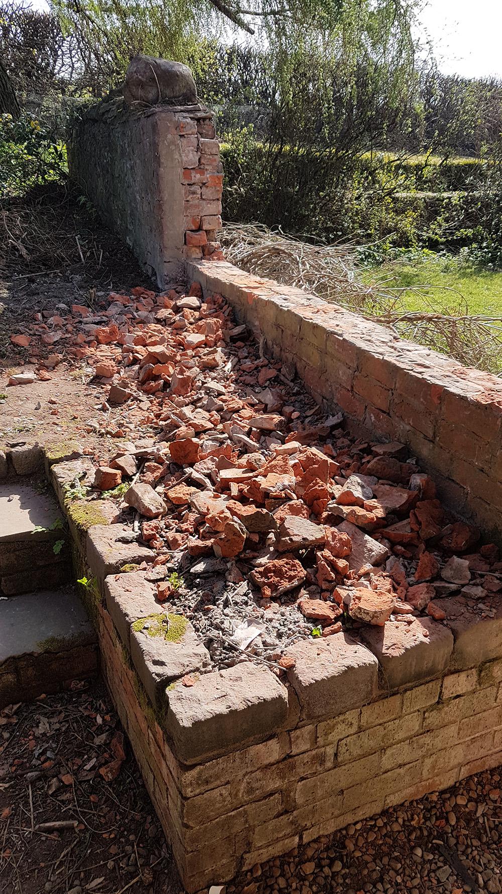 A brick wall, partly demolished.