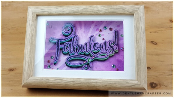 Image showing a framed die cut word in green and purple colours featuring the Fabulous cut foil and emboss die from John Bloodworth Gentleman Crafter
